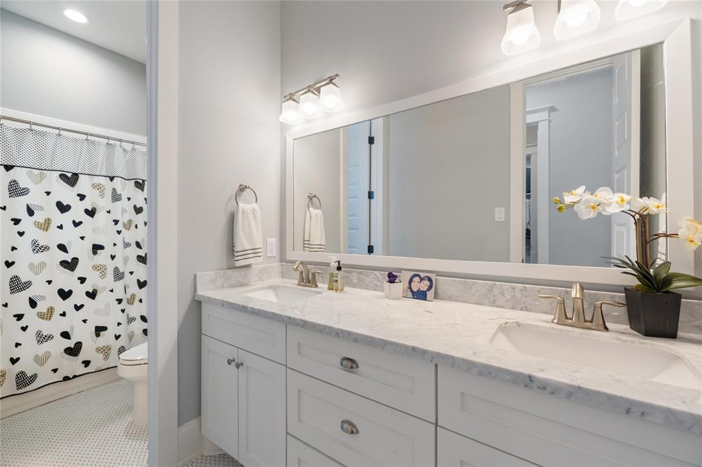 This secondary bathroom is located upstairs just off the secondary bedrooms. It includes a double sink vanity with marble counter tops, undermount sinks, and gorgeous tile work.