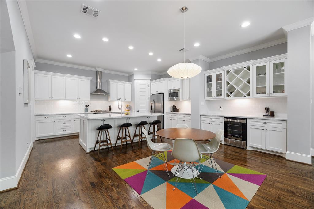 The dining room space is large enough for an 8 seat dining room table. It is open to the kitchen and the living room. The open living space includes hardwood oak floors, recessed lighting, and crown molding. It also includes a dry bar with beverage fridge, Carerra marble countertop, subway tile, and wine storage.