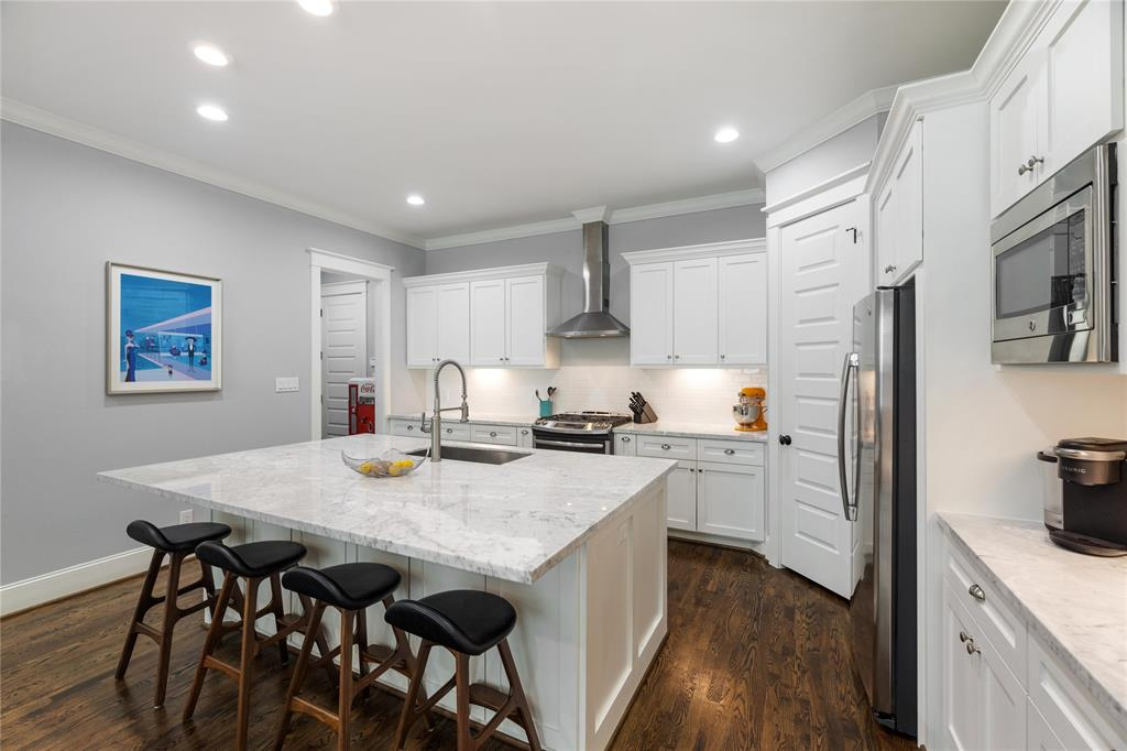 The kitchen includes a large walk-in pantry, tons of custom cabinetry, build-in microwave, Coffee Station, spice drawer, stainless steel appliances, a prostyle pulldown kitchen faucet, and a large stainless sink.