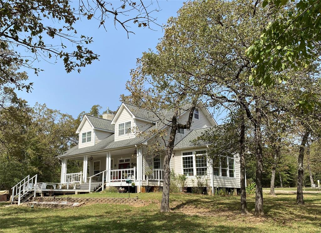 ONE OF KIND PROPERTY! Nearly 20 acres of rolling woods with a 4 acre stocked lake, trails, and park-like areas. It could serve as an income producing B & B. Located just West of I-45 between DFW, Houston and Austin!The 3,600 sq. ft., 5 bedroom (including lofts), 3.5 bath house with veranda back porch has 3 floors with top lofts serving as sleeping areas.Bunk Houseto facilitate additional sleeping and storage space close to the house.3 fully furnished, self contained cabins with their own Water, Electric and Septic.2 full RV hook-ups. The Garage/ Shop area has electricity in place. Well House pulls water from the lake to irrigate around the main house and garden area. 2 areas have Gazebos in place with trails and paths. Most of the furniture will convey (personal items excluded), retreat dishes, monogrammed linens, 2013 Kawasaki Mule 4 passenger, 1980ish 4-Wheel Drive Kubota Tractor (smaller version), Log Splitter, air compressor.   * Sellers are Licensed Real Estate Agents