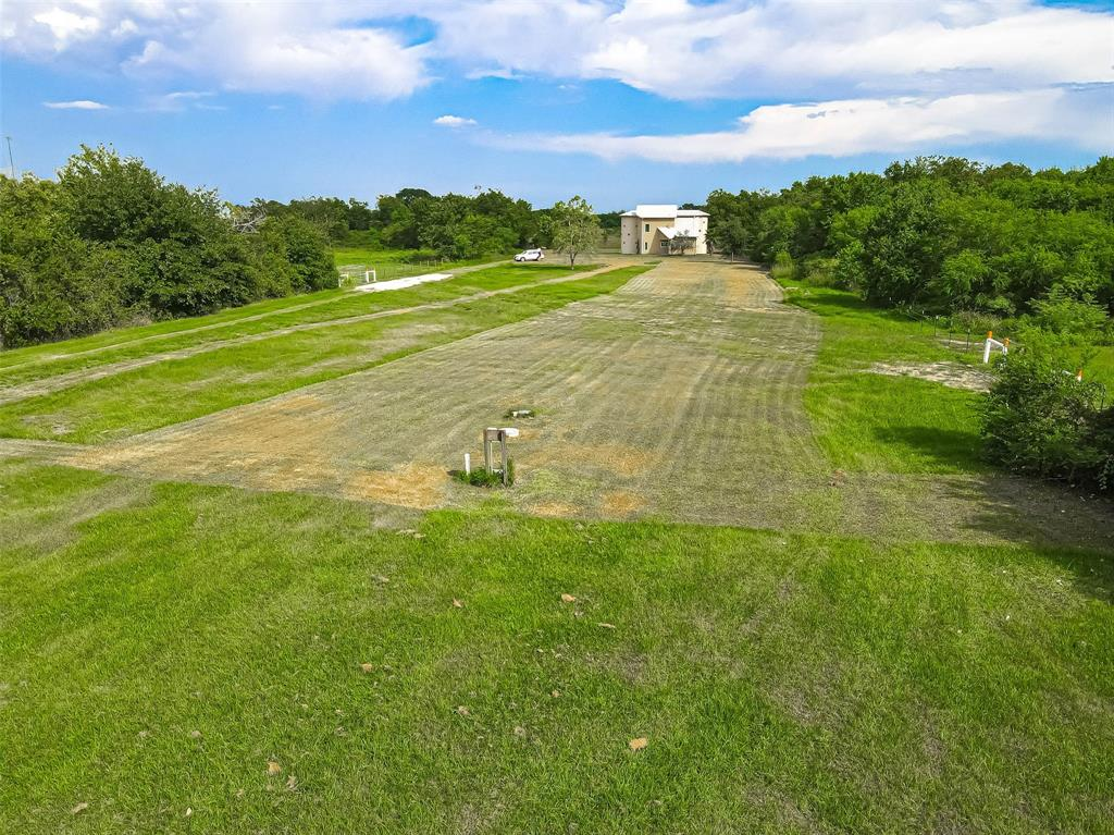 GREAT location with entry access on Highway 59. Land is 3+ acres. Survey is available. A building/home in the back of the property is not completed. (see photos) Very versatile and good opportunity to finish out, live in or use as an onsite commercial building/business. The building can be finished out and used as a home or can be turned into commercial building. Building is towards back of the property.