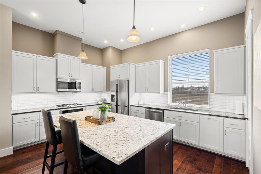 Beautiful center island kitchen with granite counter tops, subway tile back splash and stainless steel appliances.