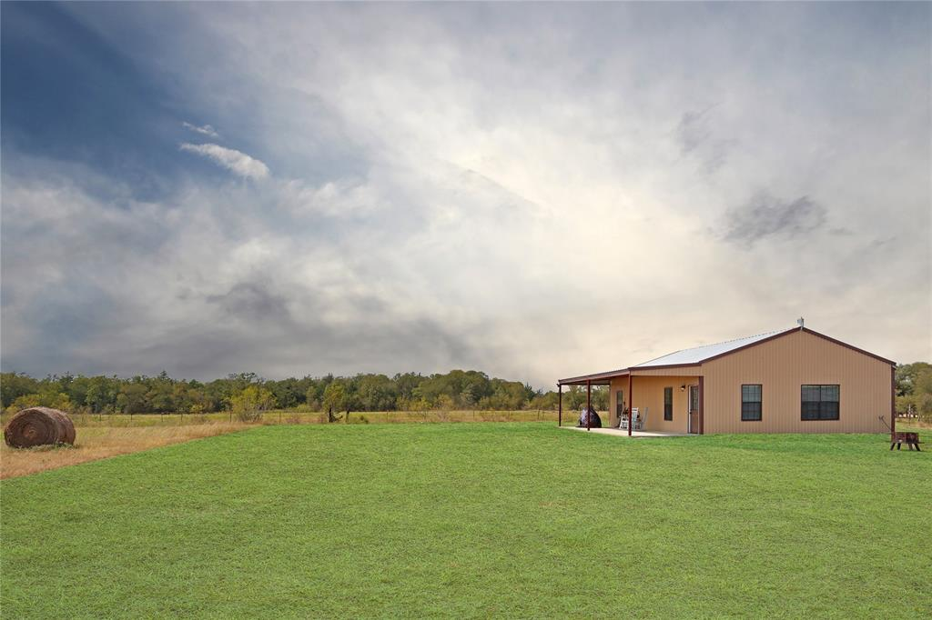 This 2018 Barndominium sits on over 10 acres. Beautiful stained concrete floors flow through the entire home, as the tall ceilings and natural light from the numerous windows make the space feel big and bright. If you are looking for privacy, this property is it! Secluded from neighbors and protected by trees, the house is tucked away on top of the hill, from the hustle and bustle of town. You don't want to miss the amazing Texas sunsets on the porch, so grab a rocking chair and come check them out!