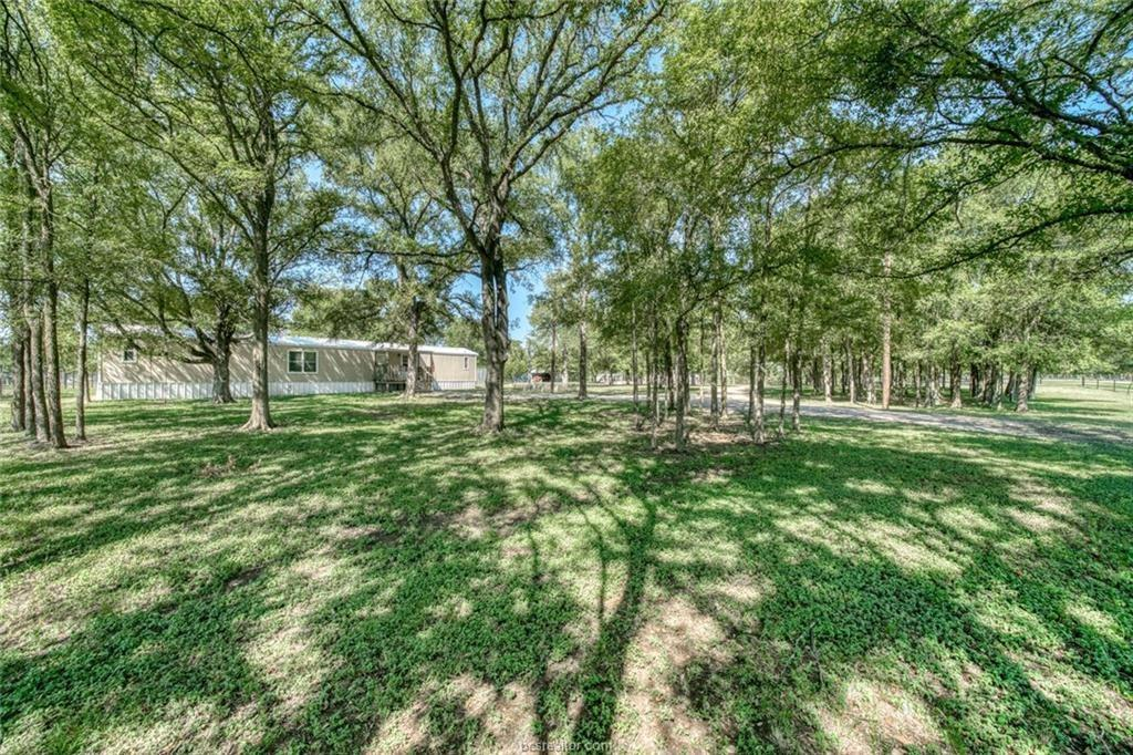 Travel on paved roads to enter this 6.256 acre property through a lovely pipe fence entry with a remote controlled gate. There is a shared pond with the neighbor which could be enlarged if that is your desire. Perimeter fencing and several outbuildings grace the property. The trees on the 6 plus acres provide shade for outdoor activities and that sure helps here in Texas on this little piece of HEAVEN! Single wide manufactured home is a clean 3 bedroom and 2 bath split plan. 2 septics and and 2 electrical connections on the property. 2 stalls, pen and barn. No Ag Exemption. New survey needed. READY FOR MOVE IN!!  Room measurements are approximate.