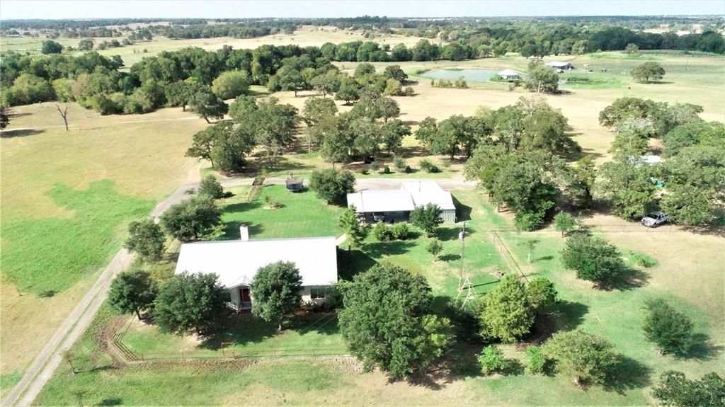 Gorgeous 2576 sf home on 103+/- ac w/125x100 sf show barn, 2 car carport w/shop w/in 5 min from town. Home inc 3 BR, 2 1/2 BA, office w/built-ins, media room, open concept living/dining/kitchen, walk-in pantry, rock fireplace, concrete countertops & floors, utility/laundry room, 10 ft ceilings, recessed lighting, fans, attic storage & more. Master bath w/double vanity, doubled headed walk-in shower, large tub, & walk-in cedar closet w/built-ins. Carport/Shop inc he & she sheds w/AC & heat, workshop, storage, spray foam insulation, & more. Show barn w/3 interior pens, concrete perimeter for back half/washing area & hay, Lee Co. water & elec, exhaust fan & more. Spring fed creek, Pecan trees, 2 stocked ponds w/docks (1.5 acres has crappie & 2 acres catfish), top-pipe fencing & elec gate. Lee County water & drilled well, electricity & water to carport/shop & barn. Chicken coop & above ground pool. Minerals neg. Please see attachment for exclusions & MANY upgrades! Inc PID's 102306 & 98443