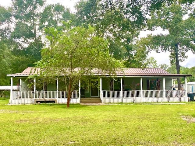 Great Location!  Ideal for county living and/or commercial business!  6.29 Acres fenced, cleared & wooded with two Street Access, FM 2100 frontage + .03 acre tract on east side of FM 2100 (across 2100). Multiple structures include 3 br/2 bath main house with two living areas, 10x70 covered front porch + covered back porch;  672 sf 1 br/1ba guest house with living room, full kitchen & laundry; 2nd Guest house 400 sf  2br/1ba, living room, kitchen & laundry; 30x50 insulated Metal Building/shop w/ hydraulic lift; 20x45 Covered RV/Boat parking; horse barn w/ tack room, chicken pens, 26 ft above- ground pool w/ deck, huge pond with cleared area surrounding.