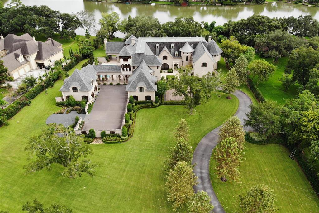 Located only 20 minutes from the Galleria, Normandy on the Lake is nestled on 3 acres amid pristine landscaping with the ebb and flow of Lake Alkire serving as the backdrop for this timeless masterpiece. Recipient of Greater Houston Builder's Association Prism Award in 2014 for design, expert craftsmanship dominates the residence with breathtaking reception hall w/dome ceiling,2 story circular library, 3 fireplaces, 2 reading rooms, spectacular arched-themed gallery, opera room, upstairs game room, elevator,luscious owner's retreat, and chef's kitchen that features crema fil tile backsplash, travertine flooring, suite of premium SS appliances & BKFT Rm w/view of glistening pool. Exquisite dining room opens to central courtyard. Observation tower provides views that are sprinkled w/countless heirloom trees while verdant grounds speak to a park-like setting. Boasting postcard-worthy views, the summer kitchen and sheltered patio are a tranquil oasis for ease of entertaining. Exceptional!