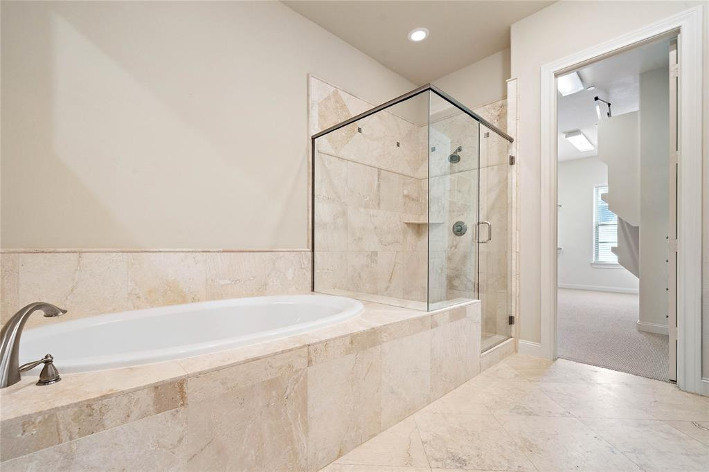 Primary bathroom with both a modern glass shower and an over sized tub.