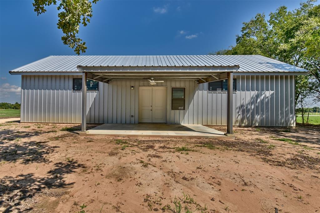 Make this newly built 1800 sf metal building on .714 acres anything you wish. It's ready for your finishing touches. The building has 12' tall plywood walls, an 18' ceiling w/extra thick blown-in insulation, new Pella windows, a completed full bath and electric washer/dryer connections. This barndominium is move-in ready but could readily be converted to multiple rooms or made into a 2-story living space. A covered 300 sf concrete patio w/ceiling fan looks onto a shaded back yard. With easy access to Hwy 290, Weimar is 85 mi from Houston and 110 mi from San Antonio.