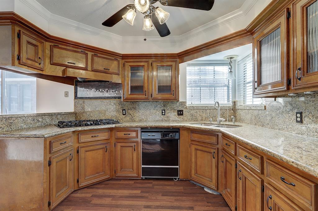 The kitchen provides access to the dining room (behind the photographer) and the breakfast room (to the left), and includes windows over the double basin sink.