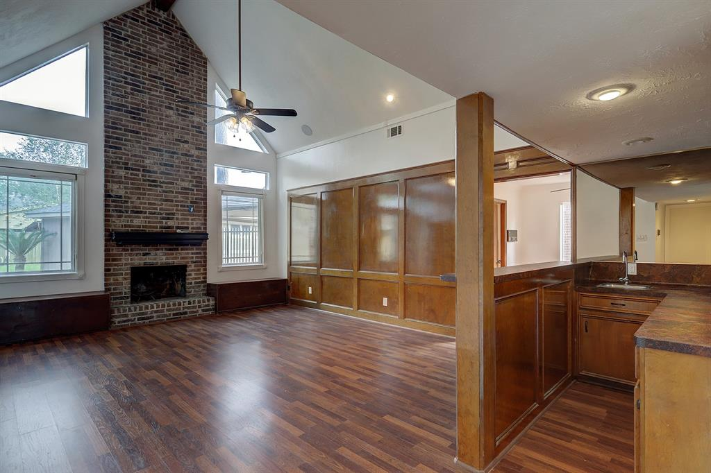 The focal point of this gracious home is the living room with a brick fireplace, cathedral ceiling, wet bar and paneled walls.