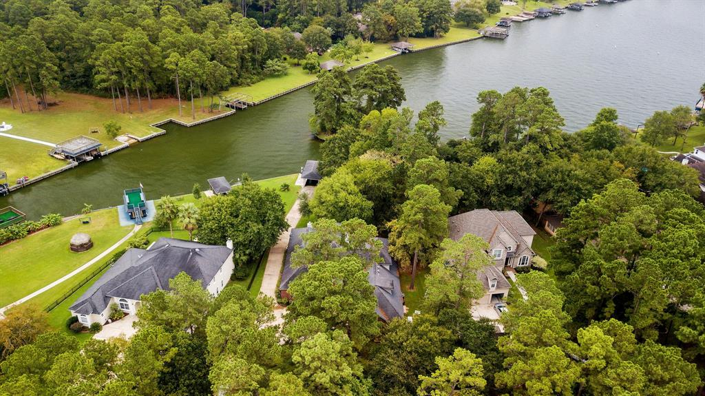 1.7 Waterfront acres on Lake Conroe  6 bedrooms + 2 study  5 1/2 Bath 2+attached garage You have your own boat launch, swim beach boat lift and jet ski lift.  Faces east for cool afternoons on the lake!  Also irrigation system for yard water from the lake ! Inside, large living room downstairs as well as  2nd floor game room  large media room. gas fireplaces in living room and master bedroom lots of large trees and huge upstairs and downstairs patios