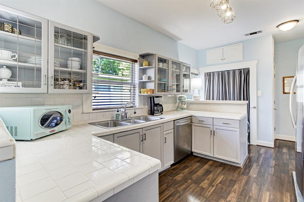 The kitchen has been updated with stainless appliances and includes additional storage in the closet at the back (behind curtains). Beautiful paned glass cabinets show off pretty kitchen ware.