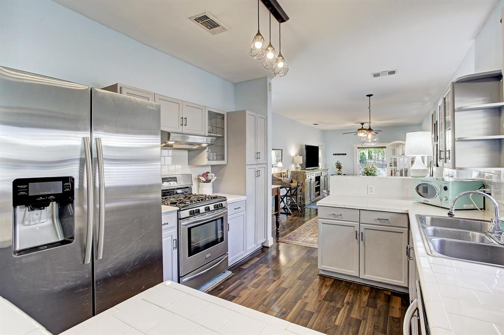 Newer lighting and pretty, neutral colors complete this living and kitchen space!