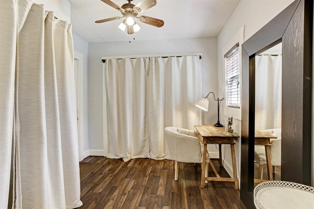 Just off the primary suite at the back of the home is an area perfectly suited for office space. The curtained closet just beyond the desk is generous, and the curtained closet to the left is the laundry. You can see the edge of the door on the left leading to the back yard.