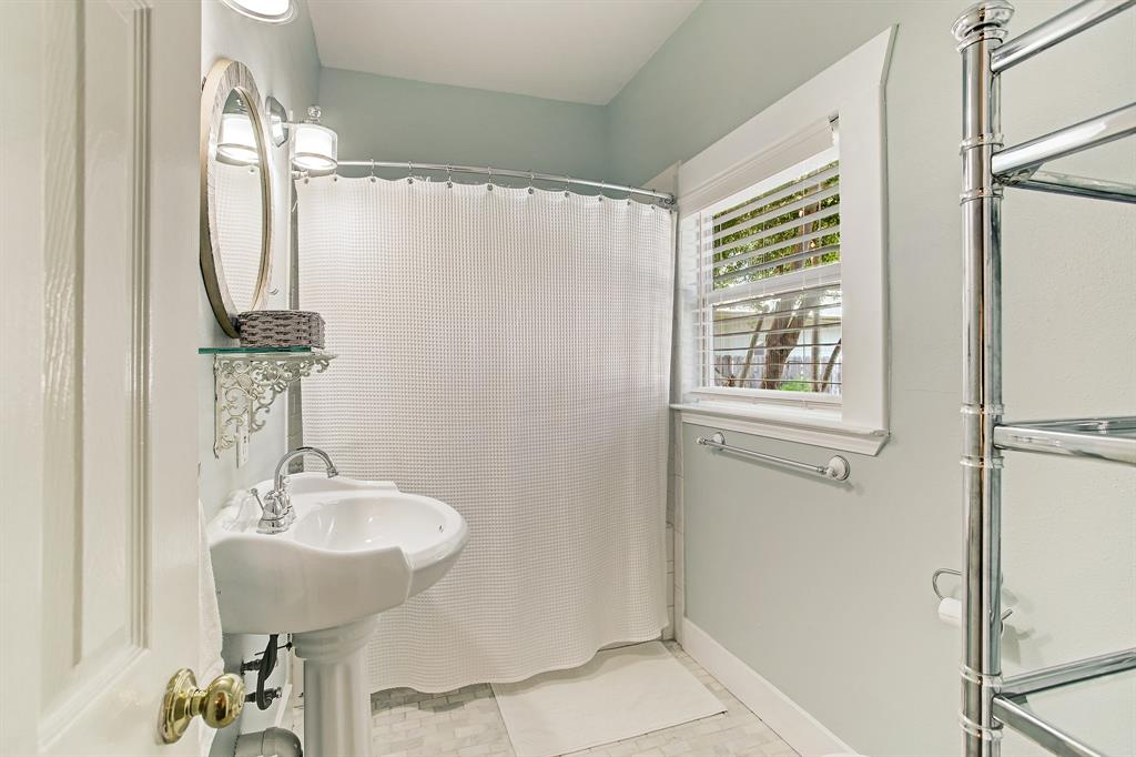 The updated, full primary bath includes a shower/tub combo, room for a shelving tower, and a window to the back yard.