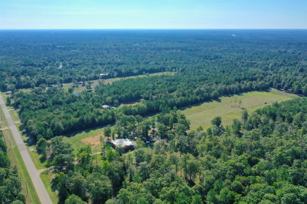 Rare, beautifully cleared and fenced 10+ acres in Peach Creek Plantation with insulated workshop, living quarters, and stocked pond! Barn is 2400 sq. feet including 800 sq. feet of living space with full kitchen and bath. Water and electric in barn. Electric goes all the way out to pond for a dock or future gazebo. There are 3 rollup doors on the barn, each 12 feet high... two of those in line to act as a pull through for tractors or RV. 800 square feet of overhead storage space with stair access. Security system. This lot is wide open with endless possibilities. Ag exemption was submitted in 2019. Septic tanks on site.