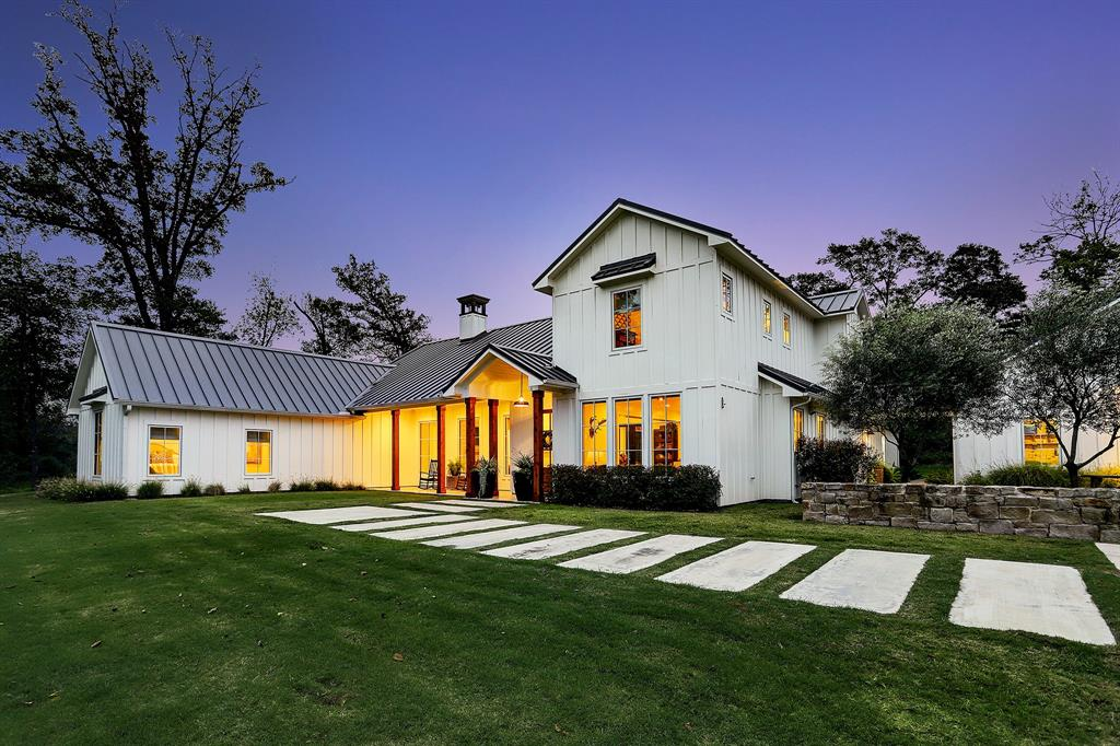 Come fall in love with this property!  Enter the 26-acre property and cross the creek bridge to gaze upon the Modern Farmhouse. The custom-built 4BD/4.5BA home is perfect for entertaining with its open concept living dining kitchen area as well as the inviting den with wet bar.  Lauren Liess, the designer of the 2020 Southern Living Idea House, designed the kitchen with its honed marble waterfall edge island. Imagine sipping your favorite beverages in the cozy breakfast nook at sunrise and by either of the fireplaces at sunset.  The property also has a 2BD/1BA apartment with a full kitchen in its large barn, which has so much capability with a large porch area and a covered RV area with a hook up.  Enjoy the views of deer and other wildlife roaming from the front courtyard, the screened back porch, or in the hot tub. The property is just 30 minutes to Round Top, and centrally located to Houston and Austin.