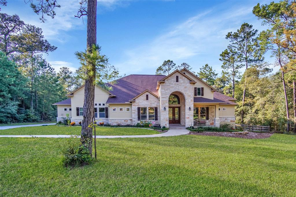 Beautiful Custom Home on 6.27 wooded acres in the front of Texas Grand Ranch.  Backs to Sam Houston National Forest.  The impressive entry greets you with high ceilings and large glass windows that look out over the pool. 4 Bedrooms each with private ensuites.  Master and secondary bedrooms have built-in closet systems and a gun closet in Master. Gameroom is connected to the Livingroom with soundproof Jeldwen sliding glass doors.  The Chef's kitchen features custom Benedettini Rustic Alder Cabinets, granite counters, under-mount lighting, soft close drawers, large walk-in pantry and Kitchenaid stainless appliances.  Bring your Boat or RV and park in the garage which features a 14 ft garage door along with 2 additional car spaces!  TREX Flooring on the massive back deck overlooks the sparkling Oasis heated Pool with a rock waterfall, slide, and Spa.  Enjoy the sunset while cooking in your outdoor kitchen on the propane grill on granite countertop with sink!  Horses and chickens allowed!
