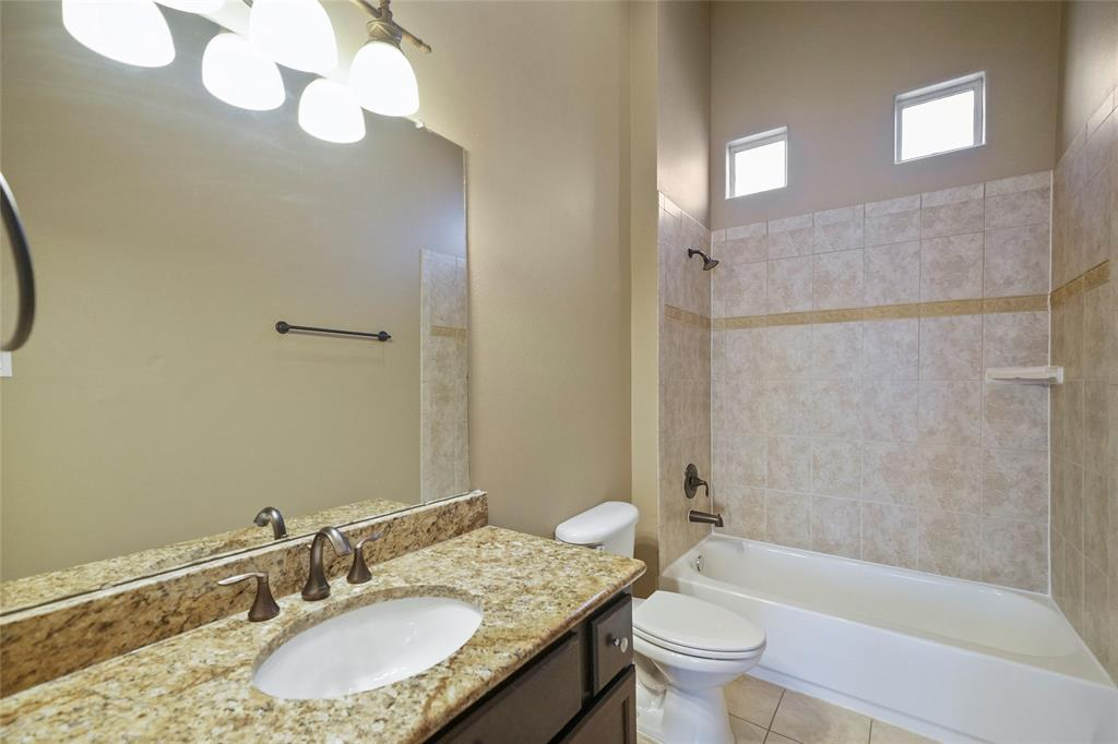 The secondary bathroom includes tile surround and floors. It also includes a vanity with great storage and granite countertops.