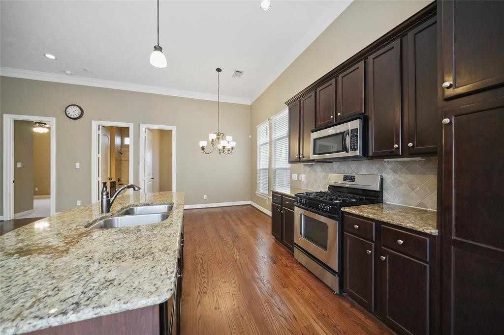 The island kitchen includes stainless steel appliances, granite countertops, and tons of cabinet space.