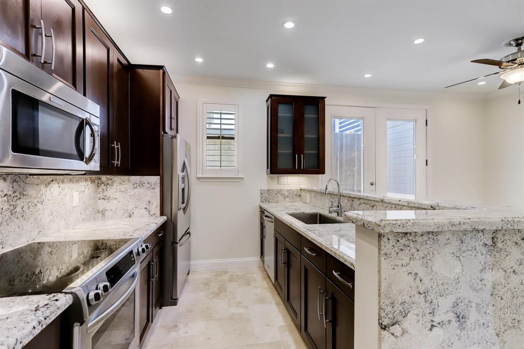 This stunning kitchen provides amazing counter and cabinet space, a single basin sink and beautiful granite surfaces.