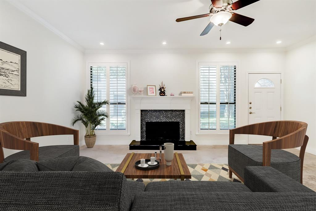 The generous living area of the home just inside the front door looks out on the courtyard and includes a wood burning fireplace. The plantation shutters here are found throughout the property. (room is virtually staged)