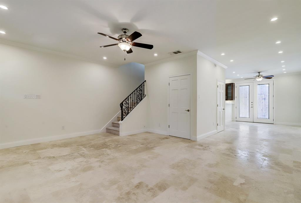 This view includes a look towards the dining area, kitchen and private patio between the home and two car garage. The door just to the right of the staircase is a big closet.