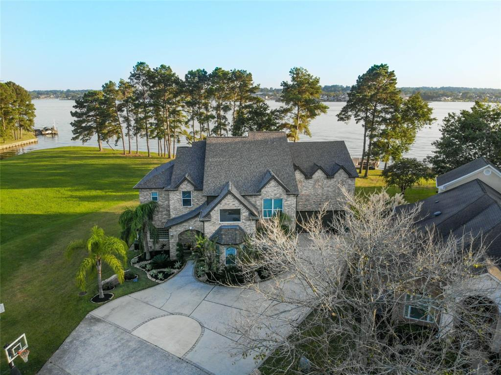Stunning Private Resort style Waterfront Home in Walden on Lake Conroe is available but will not last long!! This spectacular property offers today's amenities inside w/ stunning design & decor & a waterfront Paradise out! This Open Floor plan Beauty is dressed well in todays colors, w/ stainless steel, Bamboo wood floors, stacked stone accents & walls of glass overlooking the panoramic views of the lake. The Owner's Suite is down w/ a dazzling bath! One sees a Study & Formal Dining upon entry. A unique Flex room, down, also overlooks the lake. The Kitchen will thrill any Chef! Upstairs one has two areas in which to gather, a large balcony & 3 additional bedrooms. Outside offers fire bowls & table to gather for cool evenings, & a Generation II pool w/ hot tub and a covered sunken grilling area with a bar and underwater stools! There is a boat slip w/ lift waterside as well as floating jet ski lifts. Open Lake views, Privacy & Casual Elegance best describes this outstanding property.