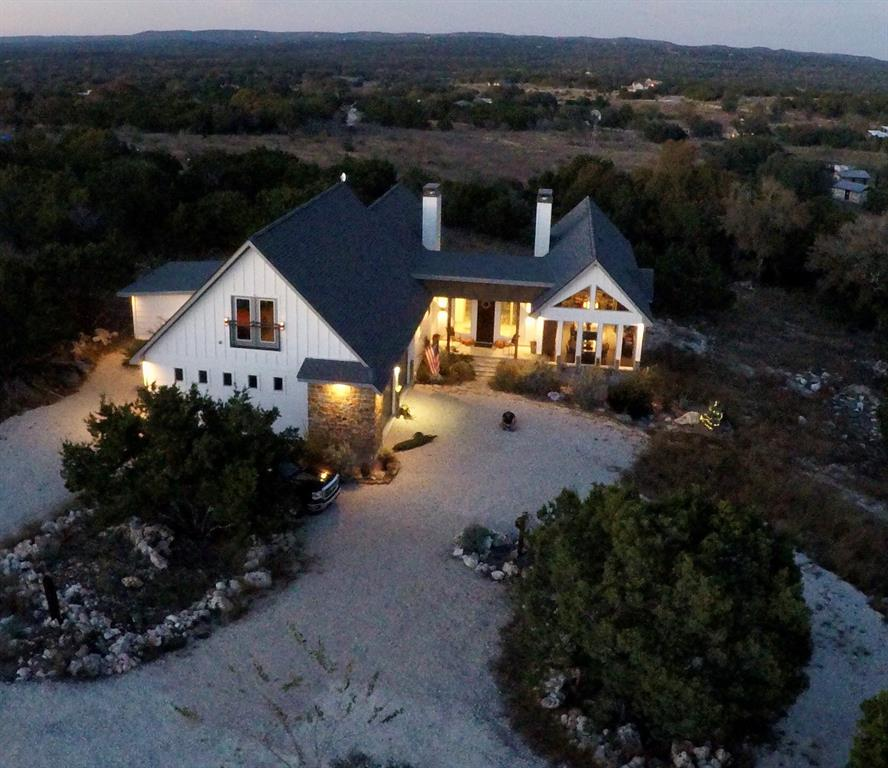 CUSTOM BUILT HOME WITH PANORAMIC VIEWS OF THE HILL COUNTRY ON 5+ ACRES. 3 BEDROOMS, 3 FULL BATHROOMS, 1 HALF BATHROOM. HOME SQUARE FOOTAGE UNDER ROOF INCLUDING COVER PATIO'S AND GARAGE IS APPROX:4300 SFT. PLUS AN ADDITIONAL OUTDOOR LIVING DECK SPACE WITH 500 SFT. 4 COVERED PATIO AREAS WITH 1 LARGE OPEN PATIO/DECK. OVERSIZE GARAGE WITH PULL THROUGH 3RD GARAGE DOOR. HOME HAS MANY  FEATURES AND AMENITIES THROUGH OUT TO LIST A FEW... 14 FOOT ISLAND WITH COOK TOP AND TELESCOPING VENT HOOD. BUILD IN REFRIGERATOR,CONCRETE FLOOR, VAULTED CEILINGS, 10 FOOT PLAT, THOMASVILLE CABINETRY, JELD-WEN WINDOWS AND DOORS, 8 FOOT STAINED KNOTTY ADLER DOORS, 2 FIREPLACES, OUTDOOR KITCHEN AREA. GUEST SUITE WITH KITCHENETTE. MANY SMART HOME FEATURES W/ WIFI LIGHTING, THERMOSTATS, GARAGE DOOR,CCTV CAMERAS, SPEAKER AND SOUND SOUND WIRING, HDMI,CABLE & CAT 6. HOT TUB & FENCED YARD. YOUR OWN PRIVATE CUL-DE-SAC FOR ADDITIONAL PARKING WITH FIRE PIT FOR OUTDOOR ENTERTAINING. GATED COMMUNITY WITH POOL,PARKS & WATER.