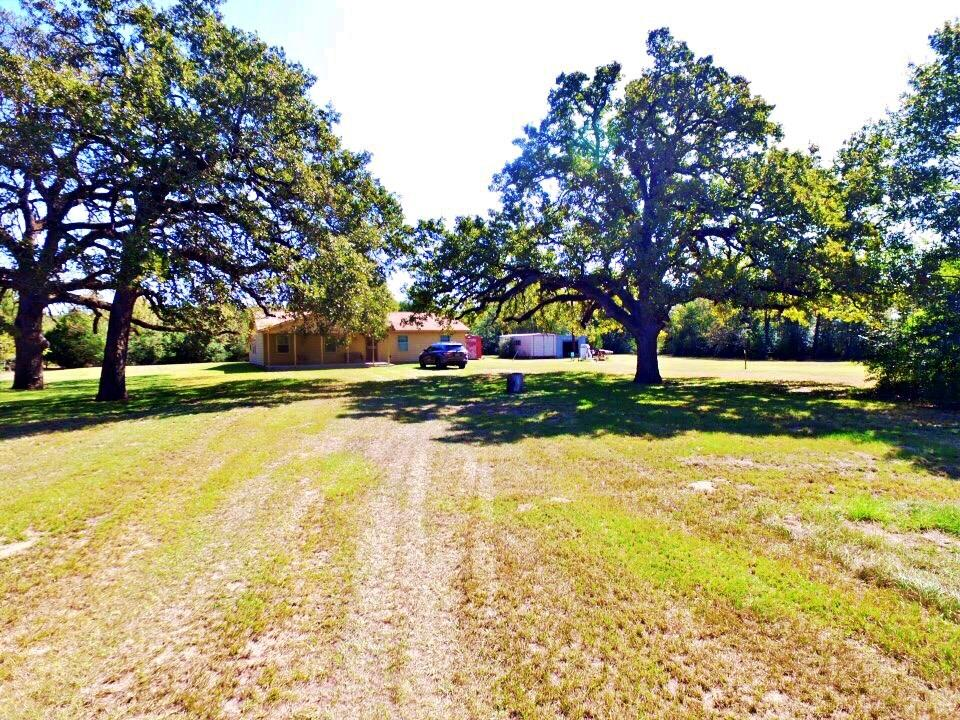 56.3 Acres of Country living at its Finest! Fall in love while taking the beautiful drive through Bryan/College Station! This Gorgeous rural acreage is located on the Corner of Greensbur and Riley and Approx 8.3 miles from all of the shopping and restaurant's, not to mention just a hop, skip and a jump from Aggieland!!  Saddle up the Horses and come on!  Country home nestled amongst  Gorgeous Oak Trees! Swing on the front porch and sip a cold one!  3 big bedrooms, 2 baths, large family room with the free standing pot belly heater will warm the entire room on a cold winter day , Large walk in pantry ! Cabinetry and all Paneling and Pantry are Ash Wood, Beamed ceiling in family room *full extra bath in one of the outbuildings outside*.Extra room on the back of the home is not included in the sq. footage . This is a peaceful private place to live, but you are Close to Everything!