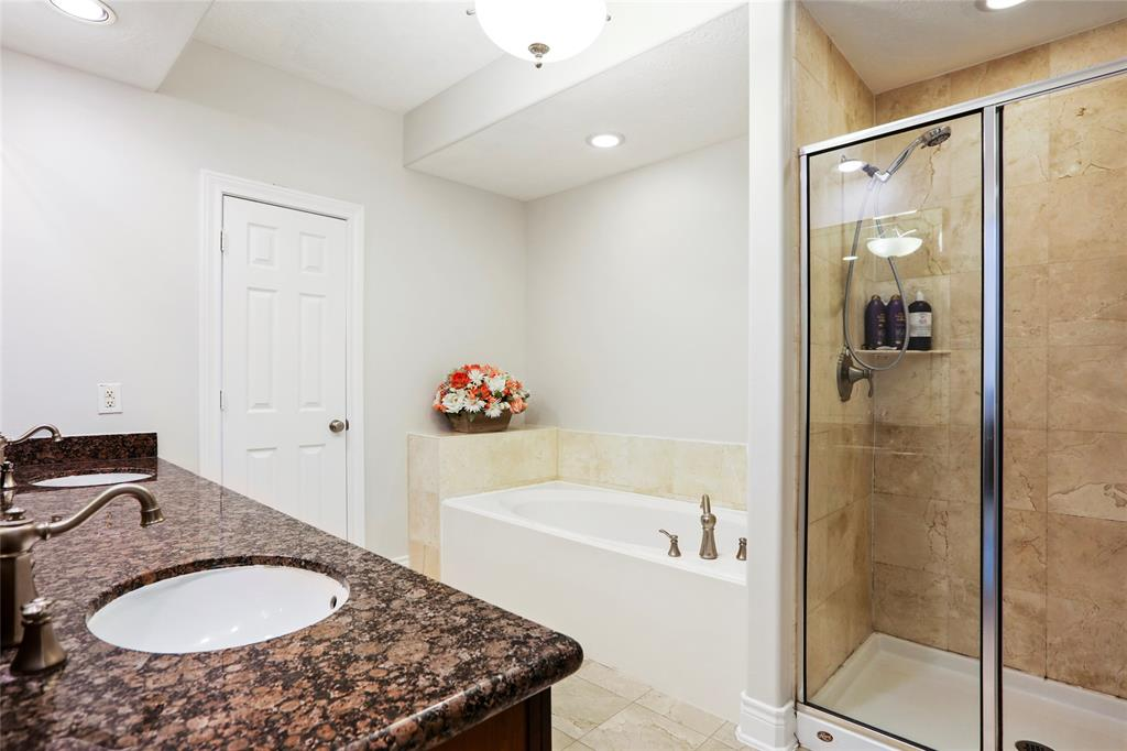The master bath also includes a large jetted tub and separate shower with tile surround.