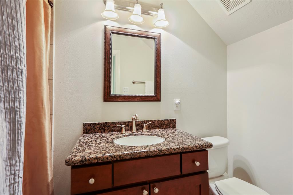 This full bathroom is located on the first floor, just off the guest bedroom. It includes granite countertops and a shower/tub combo.