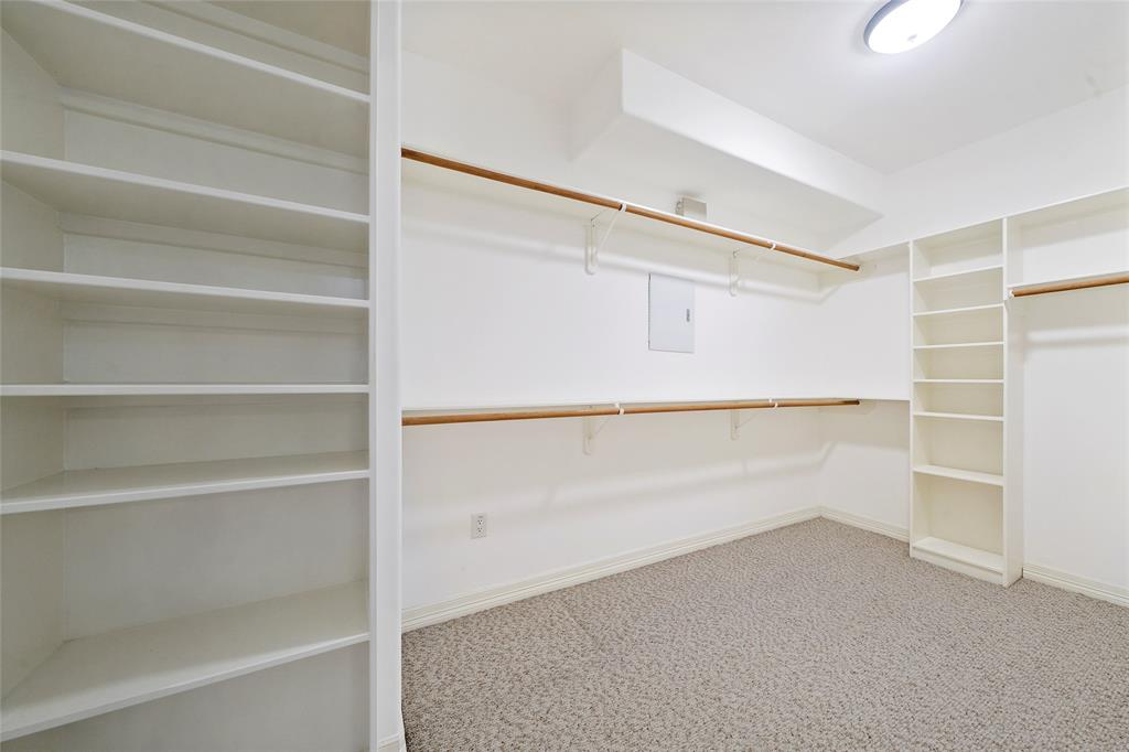 Primary bedroom large walk in closet with built ins for organization.