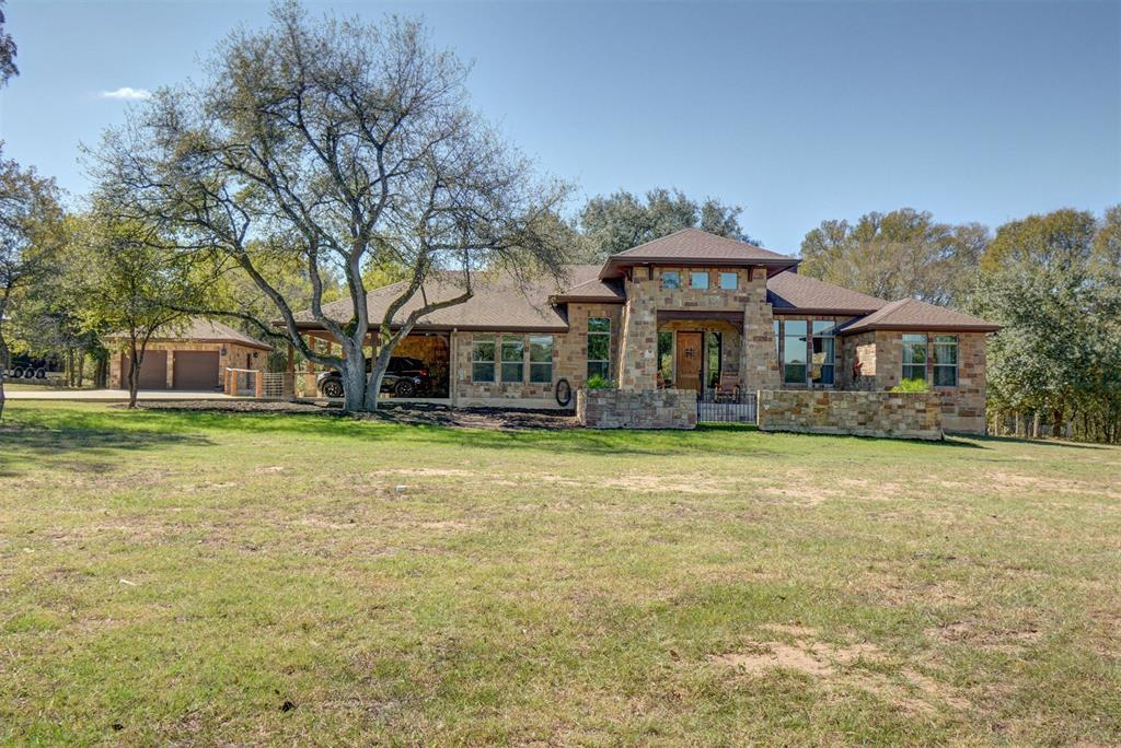 Craftsman inspired estate takes in views of 22' circumference 400 y/o live oak. Wrapped in multi-color limestone, oversized windows, high-end finishes, abundant features-giant barn/guest house. Rock 2 car garage. Home  fully spray foam insulation. Large scale exterior areas for entertaining. 15- big acreage home sites Restricted to retain beauty & allure of quiet country living, being less than 10 minutes from town. No details overlooked, gorgeous super-sized kitchen island to many closets. gourmet kitchen  commercial appliances and custom cabinetry. Floor plan & window placement offer flow & incredible views from every window. Access to the estate is a private asphalt road thru private subdivision. Stone columns, automatic iron gate lead up concrete driveway, manicured pastures to homes. Of 26 acres  2/3 is native forest. AG Exempt, sandy loam for cattle, also a great Equine facility. Main house is 2500'. Guest house is 800' of heated and cooled space,  total building 7500 per BCAD.