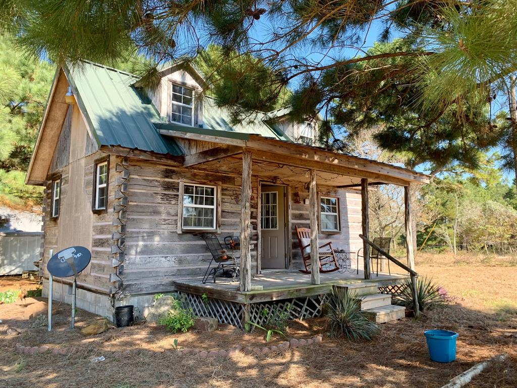 PEACEFUL RETREAT!   This adorable, rustic cabin on two acres is tucked away in the peace and quiet of the pines, just east of Grapeland off FM 227. Walking in the from the front porch, you will find a cozy kitchen, living area with an appealing fireplace, and a ladder going up to the loft/bedroom area. The bathroom is on the main level of the cabin and a back door leads you out on the back porch towards a fire pit – perfect for gathering with friends and family on those chilly east Texas nights. There is a very large shop with great storage, as well as a loafing shed for livestock. Currently there is only one other neighbor down this private road, offering lots of privacy. The square footage shown is just the main floor of this cabin-the loft adds about another 100 sq ft. This would make a great weekend get-a-way or even a full-time home for someone. Call us today to schedule an appointment to view it!