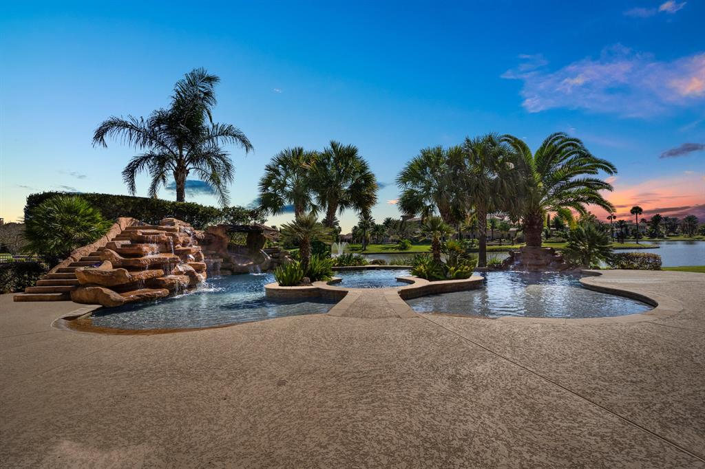 This extraordinary waterfront home is located in the guard-gated Lake Pointe Estates. Built with multi-generational accessibility in mind, it features 5 bedrooms w/ 4 & 1/2 bathrooms & offers indoor-outdoor living with elegant designer style throughout. The living spaces are surrounded by walls of windows and waterfront vistas. Chefs will love the massive open kitchen, where custom cabinetry & granite counters join upscale stainless appliances. Outside, resort-style grounds beckon with a stunning swimming pool featuring a spa, waterfalls, a stone slide, beach entry & tanning shelf. The owner's retreat offers outdoor access as well as a spa bathroom with soaking tub, walk-in shower & 2 vanities. Ascend either staircase to discover an oversized game room, 2 bedrooms, & a versatile flex room. This meticulously maintained residence features a newer roof, water heaters & iron fencing. 3 interior storage rooms, a wide motor court & 3-car garage complete the magnificent home. No MUD Taxes!