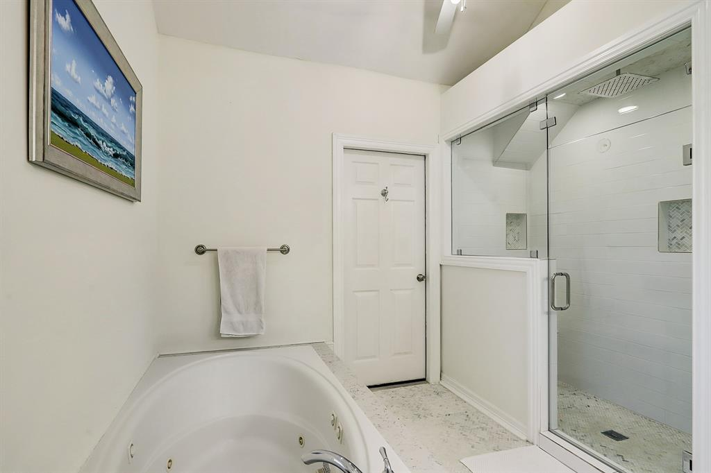 In addition to a jetted tub, the oversized frame-less glass shower stall has a bench and dual shower heads.  The closed door leads to a storage closet perfect for luggage and other non-clothes items.