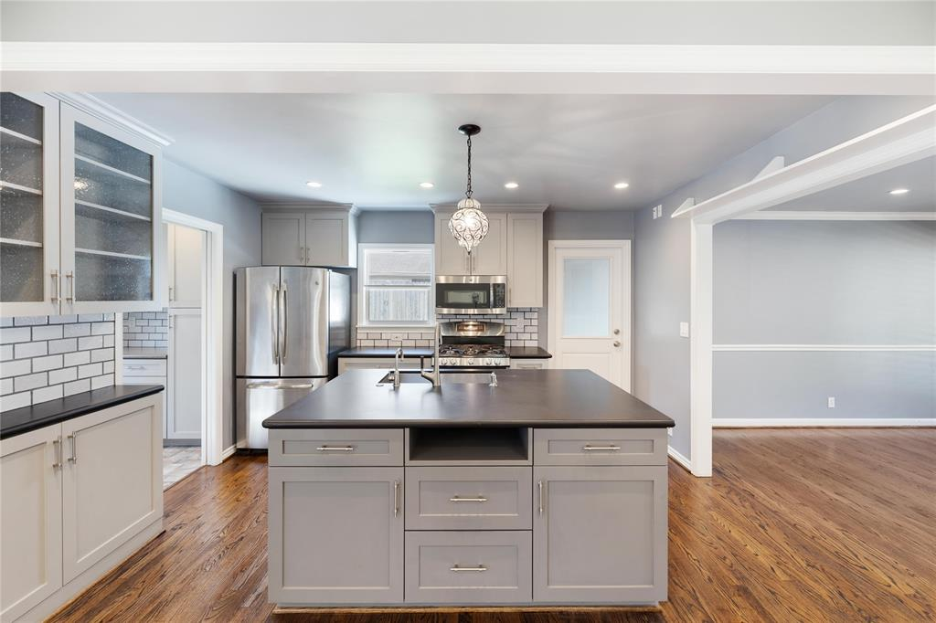 This kitchen complete with glass front cabinets and a generous island is light filled and offers the functionally desireable