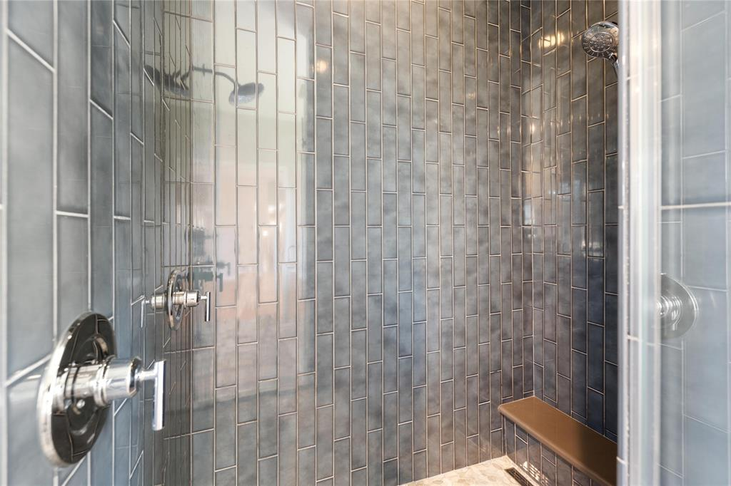 Not to be outdone by the soaking tub, the equally beautiful oversized walk-in shower stall has a bench, two shower heads, and conveniently controls for both at the frame-less glass door entry to the shower.