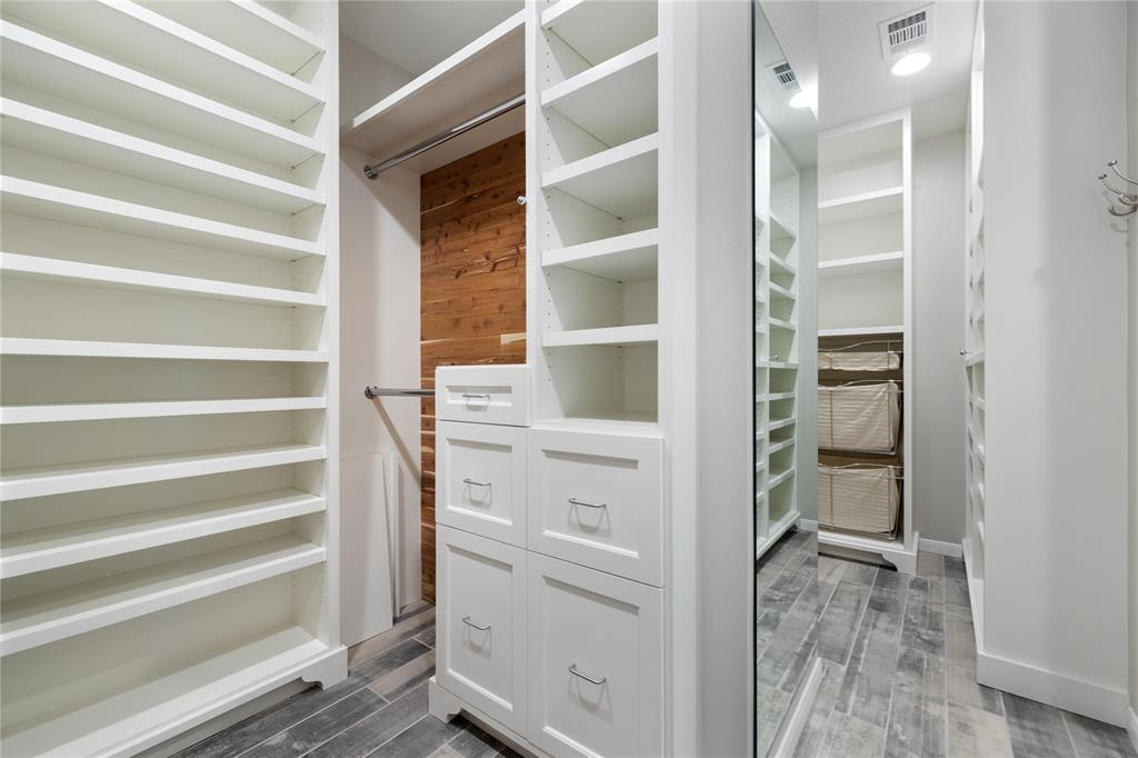 Shelf, shoe, drawer, hanging and laundry space were so thoughtfully incorporated into this magnificent closet.  A full length mirror separates the two sides at the entry.