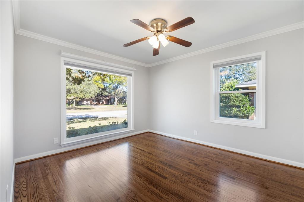 The first of the three additional bedrooms sits at the front of the home looking out on Willowbend Blvd. This room would also work wonderfully as a home office, with that beautiful picture window. There are window treatments in each secondary bedroom.