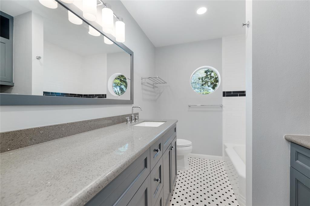 This full bath is located in the hall off the living/family room and is next to the first additional bedroom (prior photo).  The porthole style window provides light and privacy simultaneously.