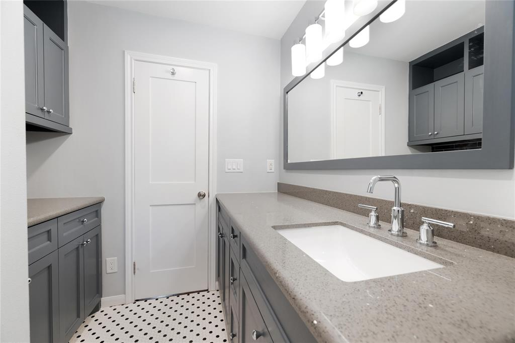 In addition to the cabinet space in the vanity, this bathroom has additional linen/storage in the bank of cabinets opposite.
