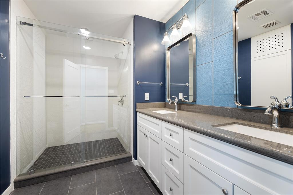 The last of the three fully updated baths includes another over-sized shower stall and dual bowl vanity. This was originally the primary bath. The clean lines and neutral finishes absolutely run throughout this home.
