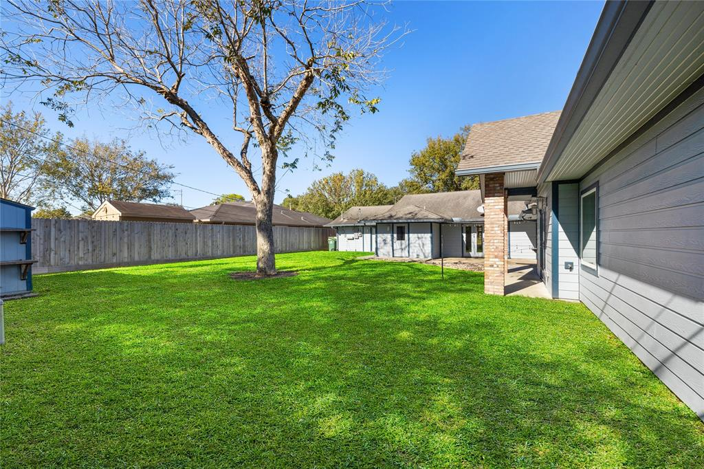 This expansive backyard is a literal canvas waiting for your outdoor design ideas! The main portion of the house is at the far end, the primary suite addition to the immediate right.