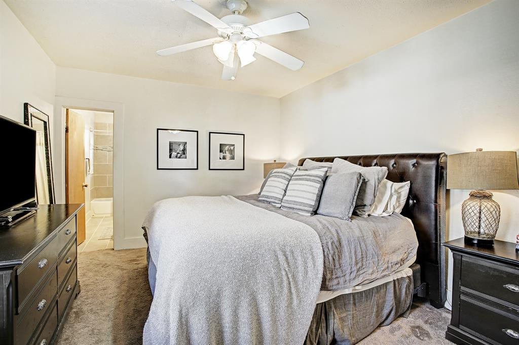 The primary bedroom is bigger than most and comfortably accepts this king bed with a substantial headboard, as well as side tables and a dresser. The private full bath is through the door at the back of the photo.