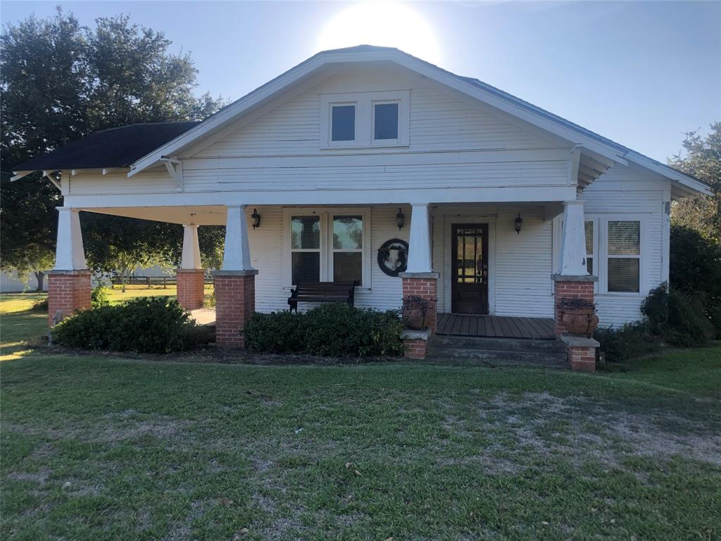 CHARMING 1920'S CRAFTSMAN ON 6.476 ACRES!! Well-built house, fruit & pozednik pecan trees. Large back patio added to home in early 2000's, w/brick/wood columns that match originals. Roomy kitchen w/built-in alcove for table. Built-in shelves, a pantry behind doors guarantee plenty of storage. Wood laminate flooring in living areas room, dining room, kitchen, new carpet in bedrooms. Big bath sits in connecting hallwayw/9 ft ceiling, acrylic clawfoot tube, pedestal sink. Central ac/heat, as well as gas jets in every room. Wood-burning stove in dining area. The property boasts a 3-slot carport w/attached office/bedroom, as well as a pole barn w/electric & water. Barn offers 3 slots with concrete floors and upward-sliding doors & 1 open 1 w/gravel floor. 14 x 24 Morgan bldg,  small storage shed. 4 of 6 acres are fenced and are accessed over a cattle guard. Coastal hay, hog pen with water, working water trough. County Rd runs behind entire property.