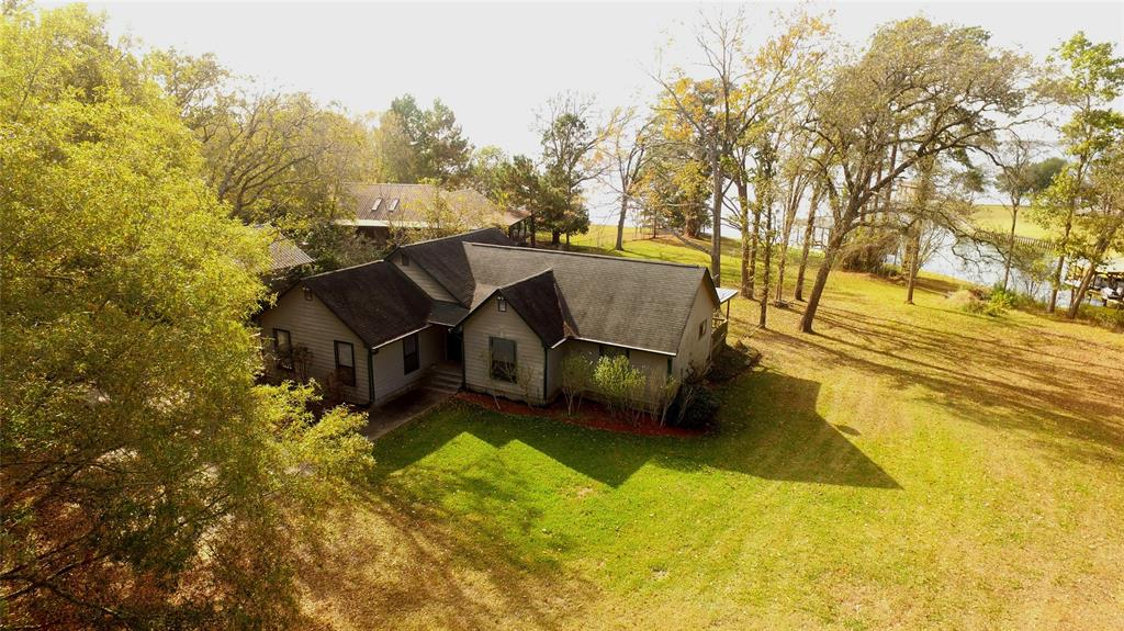 Rare Waterfront home with large acreage attached. Well maintained home with 2 living areas.  Addition Detached Garage-workshop with partially finished garage apartment (build out as you desire).  Large boathouse with storage, boatlift and double jetski lift.  Boathouse has spider misting system and lake water pump to provide water to the expansive yard.  Large enough to hunt deer and other wildlife. Most of the acreage is in ag timber exemption to keep you taxes low.  Primary bedroom has wonderful view of lake from primary bedroom, kitchen, dining and family room.  Utility Room is in closet in 2nd bedroom.  The large den is great for entertaining at the lake with room for pool table and other games and could also be used as a bunk room for extend family or guests. Plenty of acreage to create 4 wheeler trails or walking trails.  Extra equipment storage attached to the large garage workshop/apartment and large RV storage.