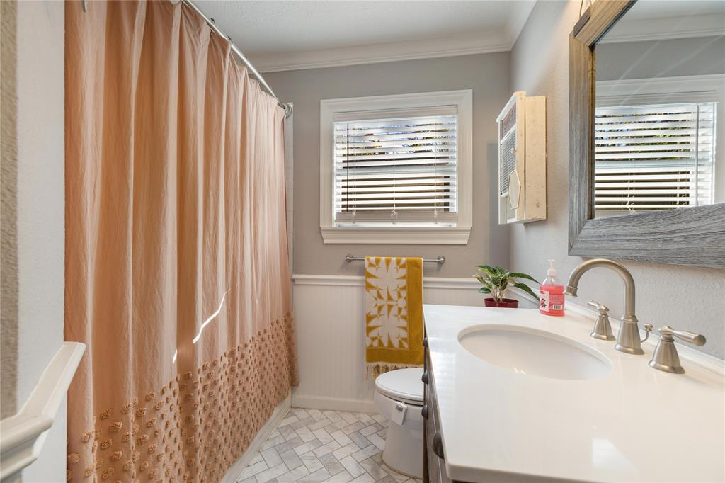 The renovated bathroom has been updated with classic finishes such as the marble tile.